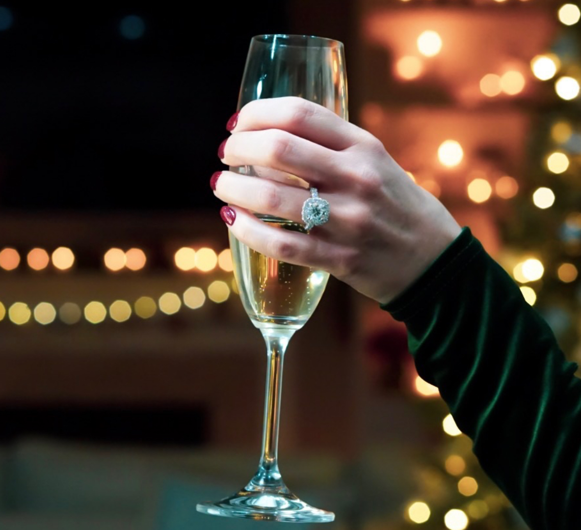 womens hand with a large engagement ring holding a champagne glass