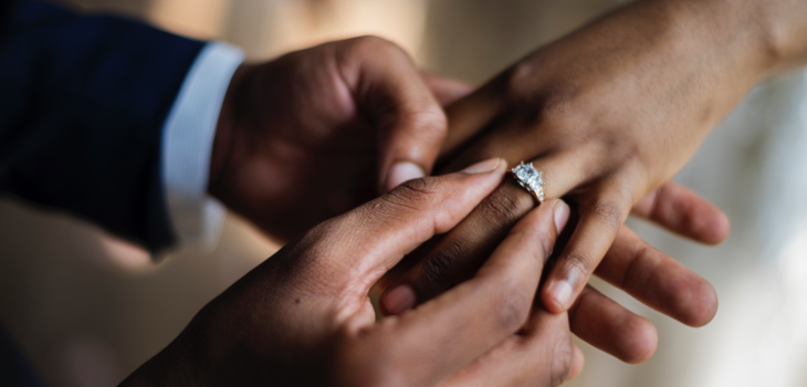 male hand sliding a ring onto the ring finger of a female hand